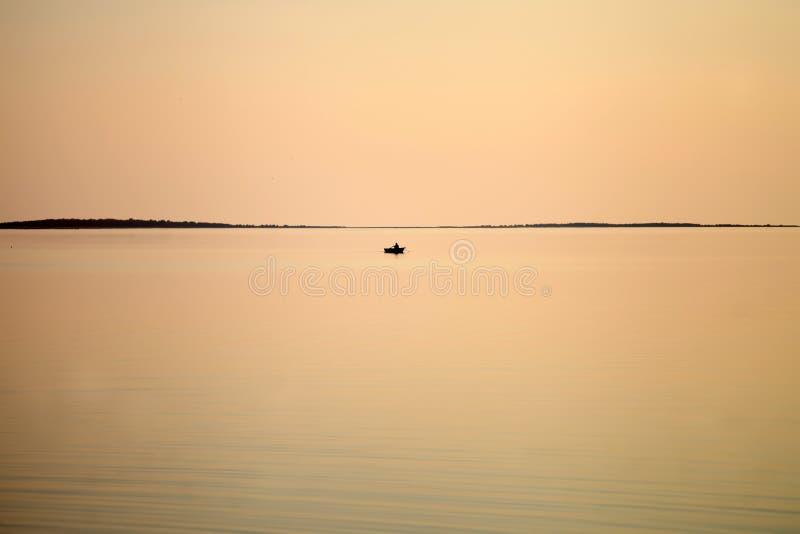 Barco de vela en el mar en el color de coral por la noche la luz del sol, lujosa aventura de verano imagen de archivo
