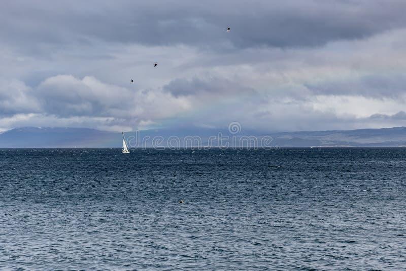 Barco de vela en el mar, visto de distancia en cielos tempestuosos Arco iris encendido fotografía de archivo