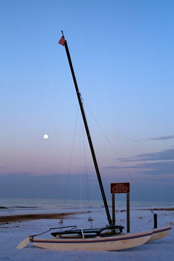 Barco de vela en la playa con la luna fotos de archivo