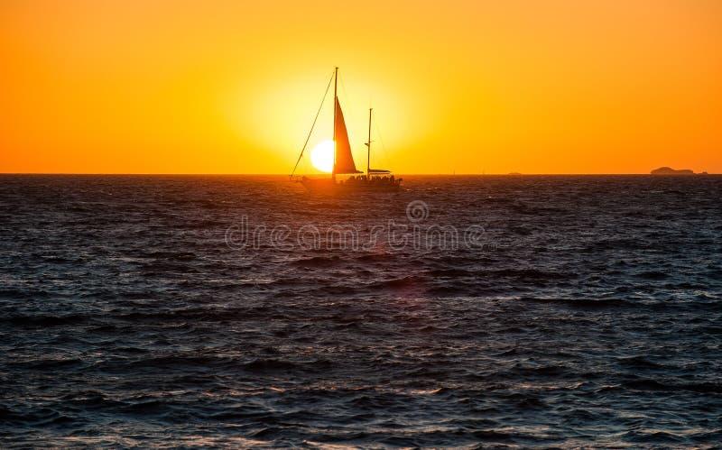 Barco de vela en la puesta del sol en el agua imagen de archivo
