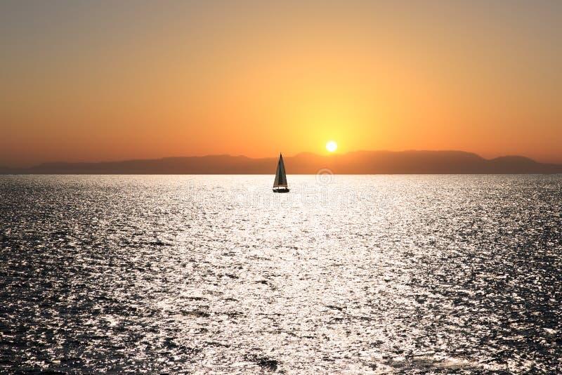 Barco de vela en una puesta del sol imagenes de archivo