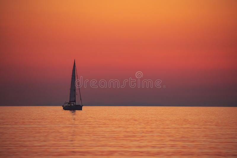 Barco de vela sobre puesta del sol fotos de archivo