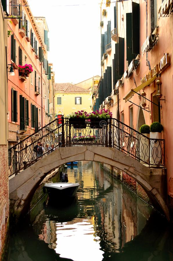 Barco debajo de un puente sobre un canal de Venecia imagen de archivo