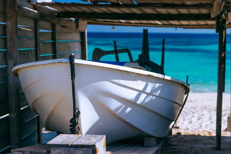 Barco debajo de un toldo contra el mar azul imagenes de archivo