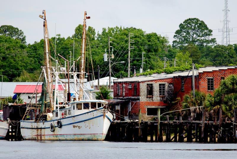 Barco del camarón atracado en un embarcadero de madera fotografía de archivo