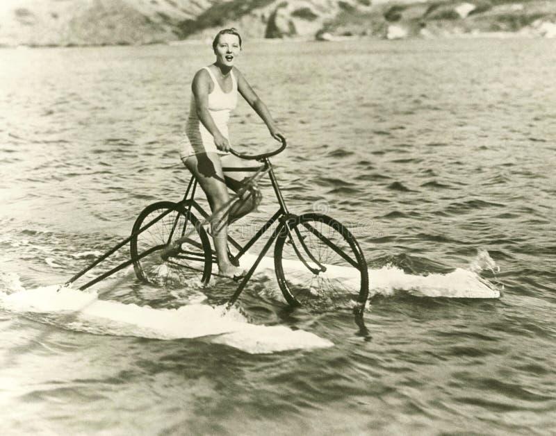 Barco del ciclo del montar a caballo de la mujer en el lago foto de archivo libre de regalías