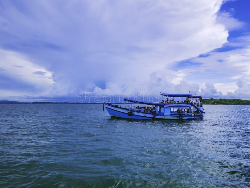 Barco del hombre de Fisher con el océano idílico y el cielo hermoso imagenes de archivo