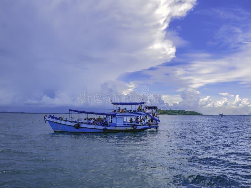 Barco del hombre de Fisher con el océano idílico y el cielo hermoso fotos de archivo