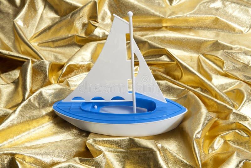 Barco del juguete en ondas de la tela del oro imagenes de archivo
