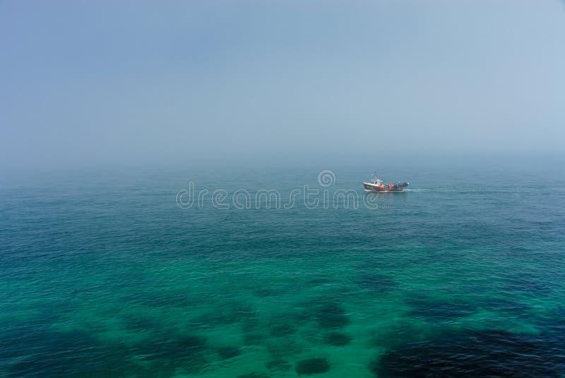 Barco del pescador en el mar brumoso fotos de archivo