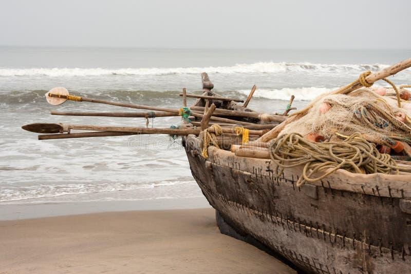 Barco del pescador por completo con el engranaje en la playa foto de archivo