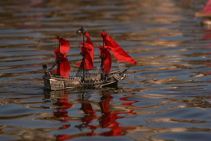 Barco del pirata con las velas rojas imagenes de archivo