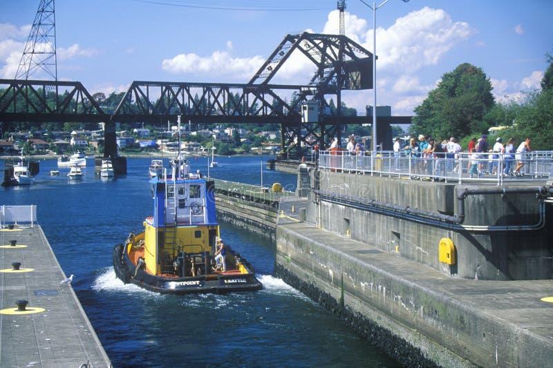 Barco del tirón que pasa a través de Hiram M Cerraduras en Puget Sound, Seattle, WA de Chittenden foto de archivo