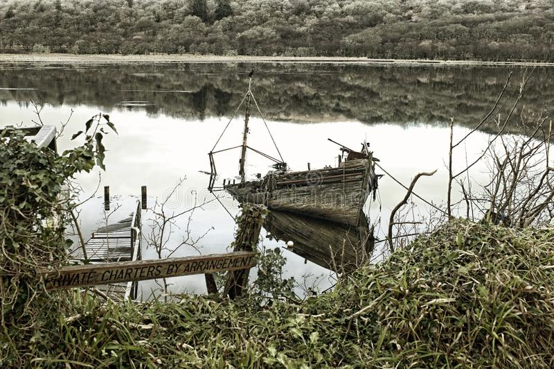 Barco destruído e abandonado no Loch ocidental, Tarbert em Argyle e Bute, Escócia fotos de stock