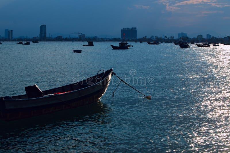 Barco do pescador no mar Luz do por do sol silhueta da cidade em uma linha do horizonte fotografia de stock