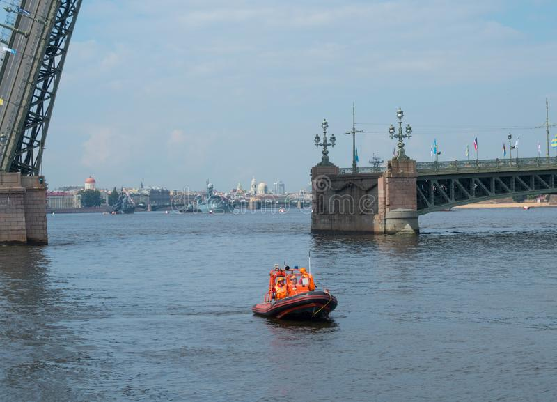 Barco do serviço de salvamento no fundo de uma ponte divorciada em St Petersburg, Rússia fotografia de stock