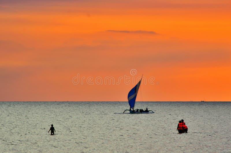 Barco do windsurfe no mar e no por do sol vermelho fotografia de stock