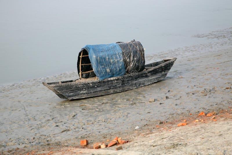 Barco dos pescadores encalhados na lama na maré baixa na cidade de colocação em latas próxima de Malta do rio, Índia imagem de stock royalty free