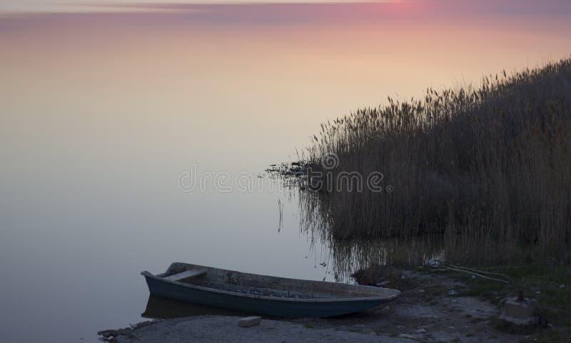 Barco e lago no por do sol imagens de stock royalty free