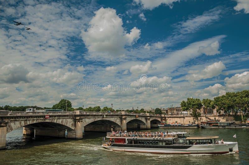 Barco e ponte turísticos sobre o Seine River sob um céu azul ensolarado em Paris fotos de stock royalty free