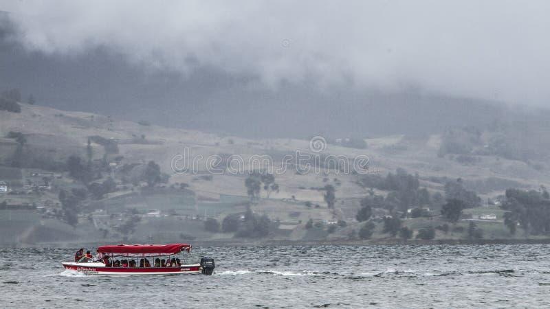 Barco em um lago ao redor das montanhas fotografia de stock