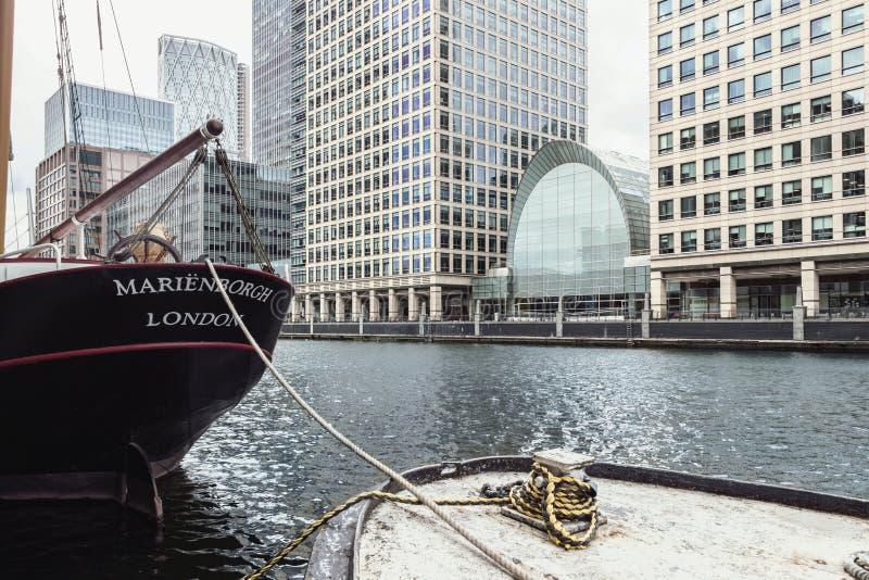 Barco en el agua con edificios modernos en Canary Wharf fotos de archivo