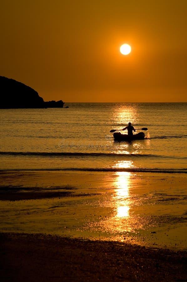 Barco en el agua en la puesta del sol, playa de Porth, Cornualles, Inglaterra fotos de archivo