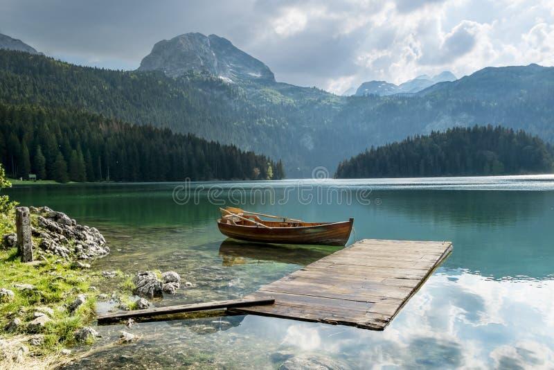 Barco en el lago negro en el parque nacional Durmitor y montañas i foto de archivo libre de regalías