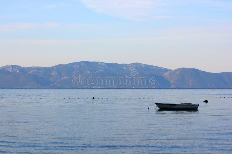 Barco en el mar con una salida del sol hermosa imagenes de archivo