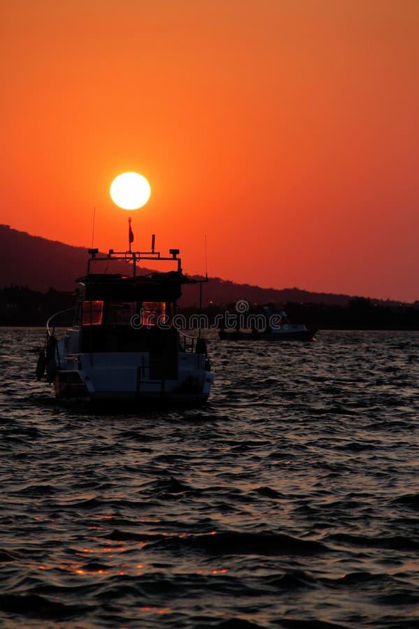 Barco en el mar en la puesta del sol imagenes de archivo