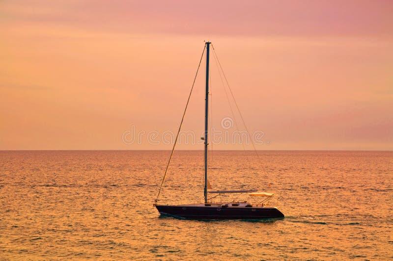 Barco en el mar en tiempo de la puesta del sol fotos de archivo libres de regalías