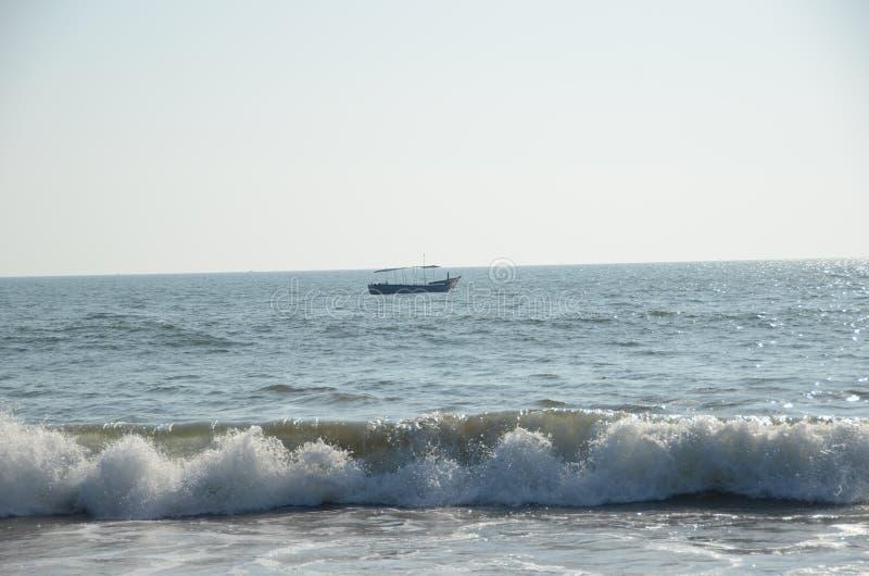 Barco en el océano con las ondas que ruedan adentro imagenes de archivo