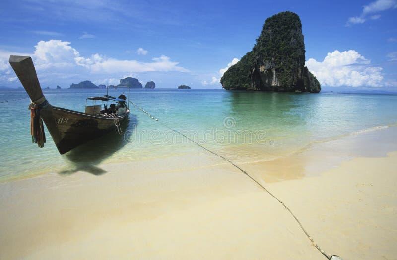 Barco en la formación de roca solitaria de la playa en fondo foto de archivo
