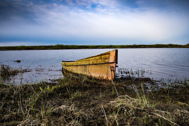 Barco en la orilla del río en la puesta del sol imagen de archivo