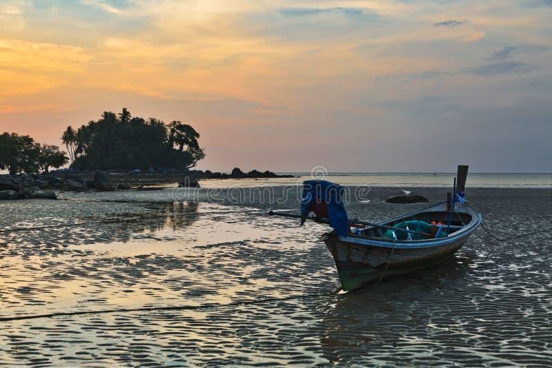 Barco en la playa en la puesta del sol imagen de archivo