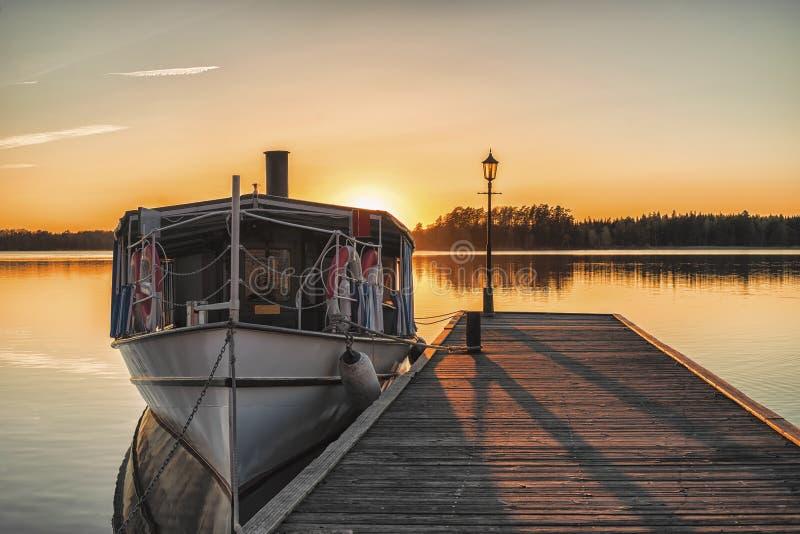 Barco en la puesta del sol de madera del durin del embarcadero fotos de archivo