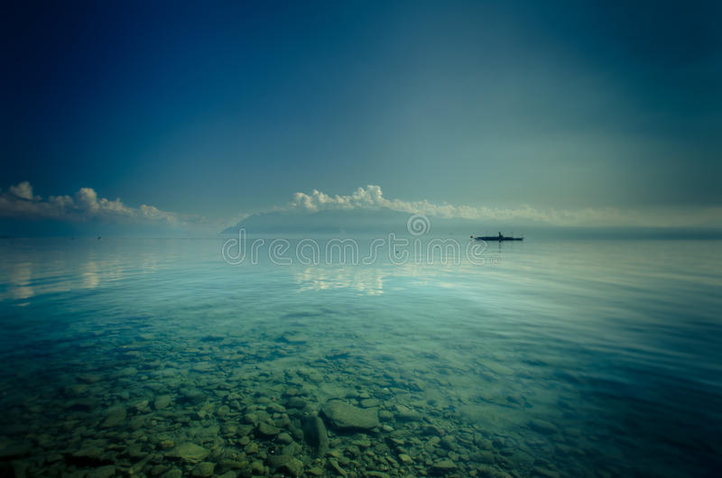Barco en las aguas transparentes del lago fotos de archivo