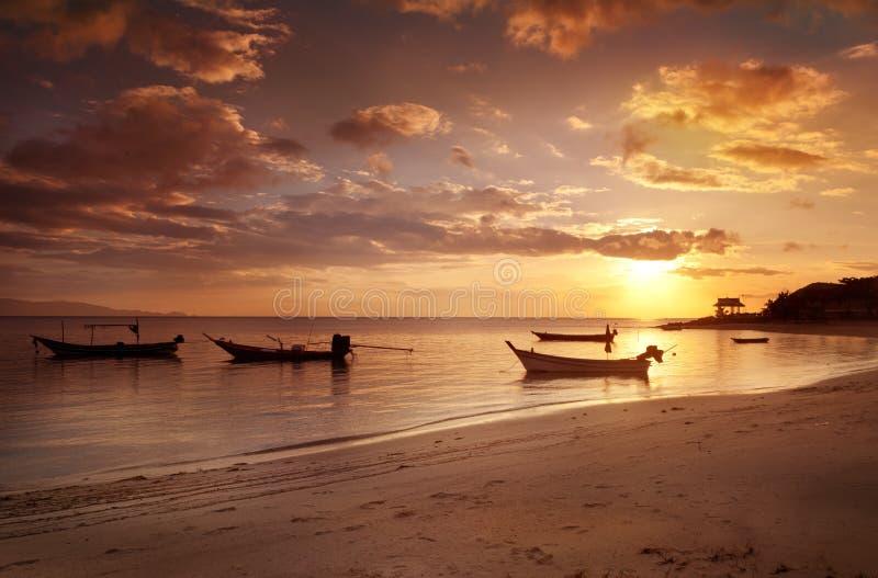 Barco en las ondas en la puesta del sol, paisaje marino foto de archivo