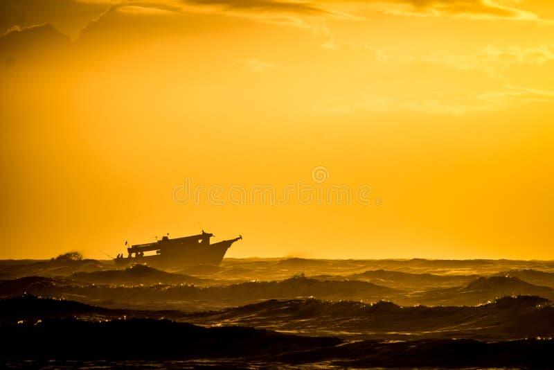 Barco en una salida del sol amarilla fotografía de archivo