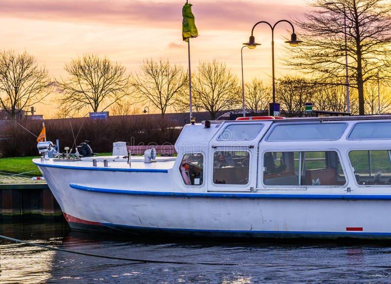 Barco entrado no porto no por do sol, céu colorido no alvorecer, veículo do transporte da água fotos de stock