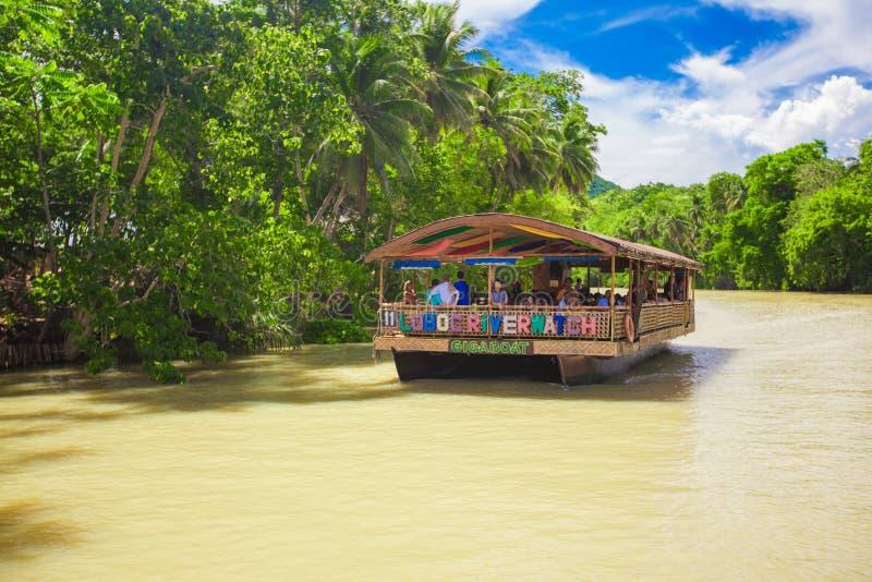 Barco exótico de la travesía con los turistas en el río de la selva foto de archivo libre de regalías