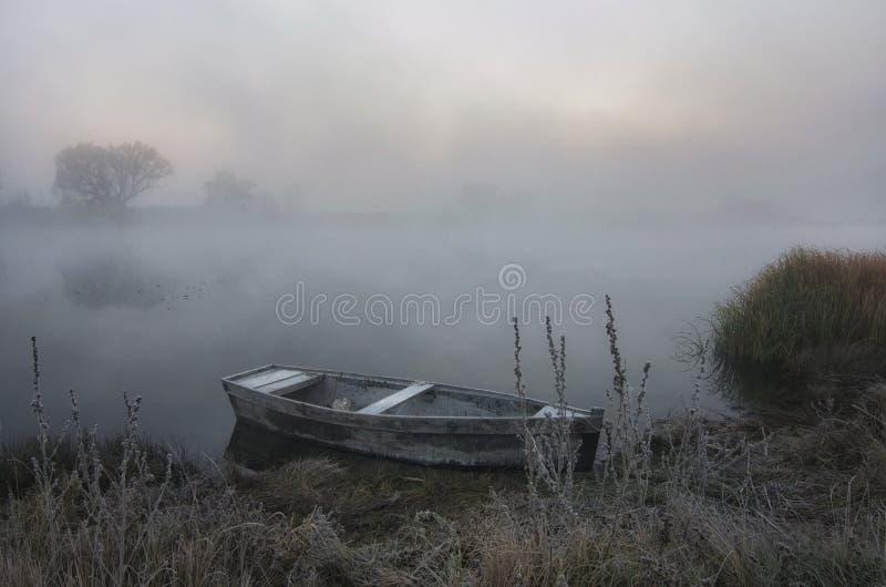 Barco fora da costa em uma manhã nevoenta da mola foto de stock