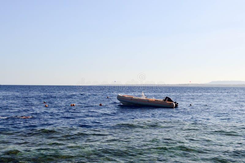 Barco gris inflable, un barco de motor con un motor en un mar azul de la sal contra el contexto de montañas distantes imágenes de archivo libres de regalías