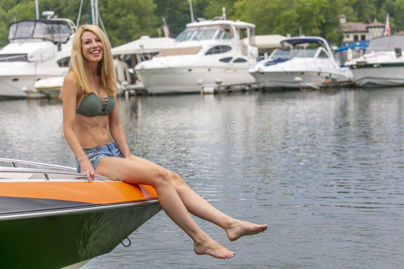 Barco hermoso de Relaxing On A del modelo del bikini por los muelles imagen de archivo