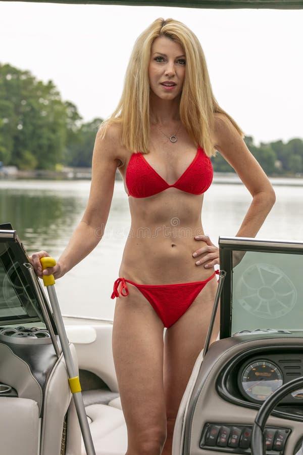 Barco hermoso de Relaxing On A del modelo del bikini por los muelles foto de archivo