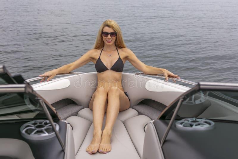 Barco hermoso de Relaxing On A del modelo del bikini por los muelles fotografía de archivo