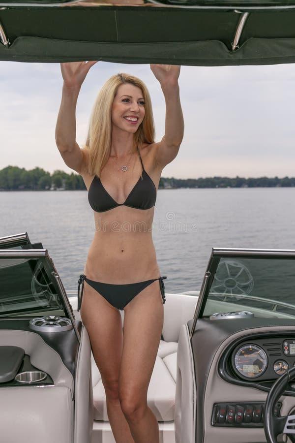 Barco hermoso de Relaxing On A del modelo del bikini por los muelles fotos de archivo