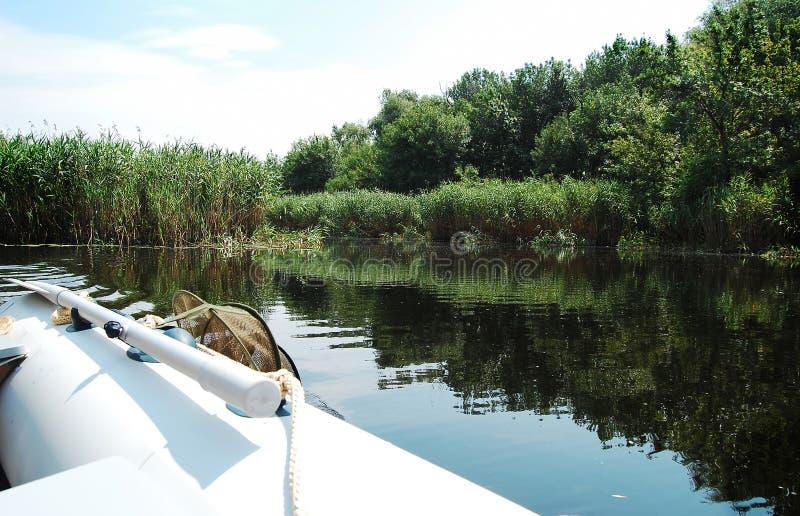 Barco inflável em um rio estreito no meio-dia imagem de stock