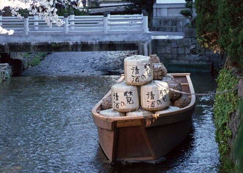 Barco japonés con las mercancías en un río atado al banco con un fondo de la cuerda imagen de archivo libre de regalías