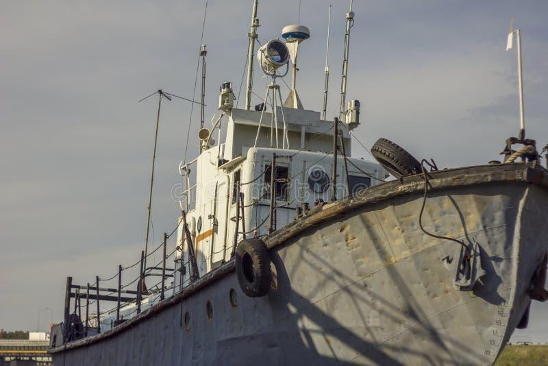 Barco largo oxidado viejo anclado en el embarcadero fotos de archivo